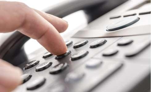 Finger hitting telephone number keys